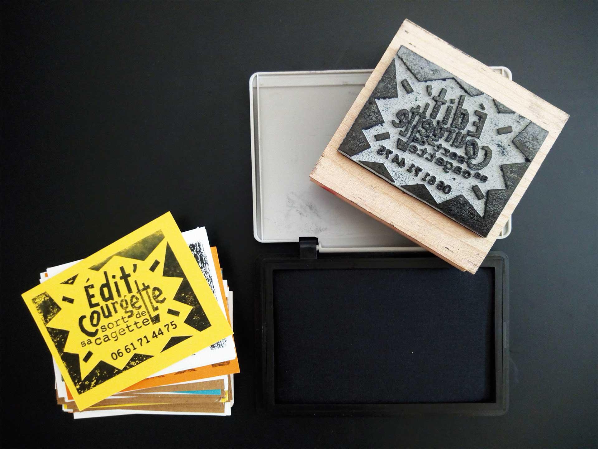 Tampon encreur en bois avec boitier d'encre et petites feuilles de carton colorées servant de carte de visite